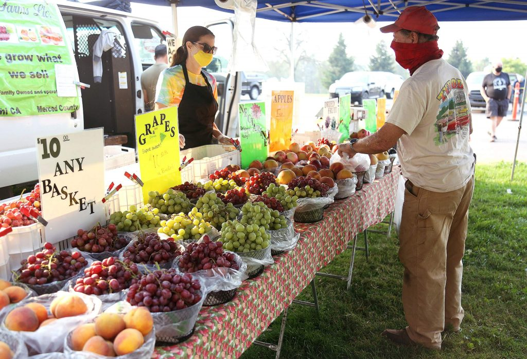 Lin Sauls of Ponce Farms serves a customer Thursday morning at the Penn Valley Farmers' Market at Western Gateway Park, where many local vendors have been selling their goods. The market will continue  from 9 a.m. to 1 p.m Thursdays.