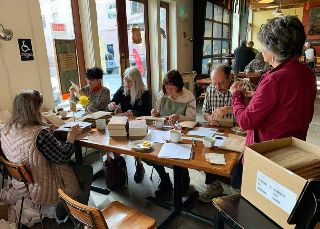 A mailing party, held at Three Forks Bakery & Brewery, to send out copies to the 145 contributors to the anthology.