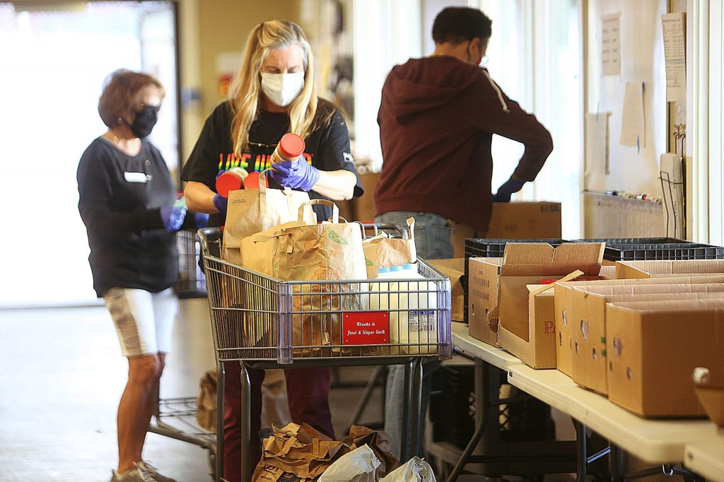 United Way volunteer Megan Timpany and other volunteers do the shopping for clients as they wait outside in their vehicles.