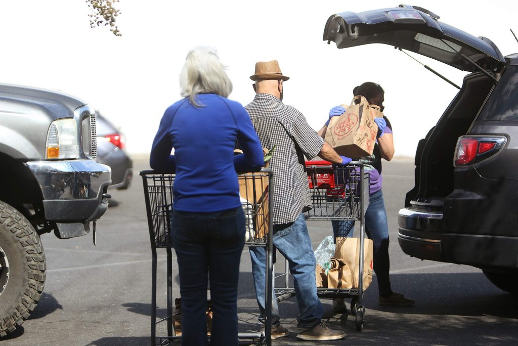Food Access Saturday workers help to load vehicles with groceries during the second Saturday drive-thru food distribution in the parking lot of Interfaith Food Ministries in Grass Valley. The Saturday food access program is made possible through a partnership with United Way.