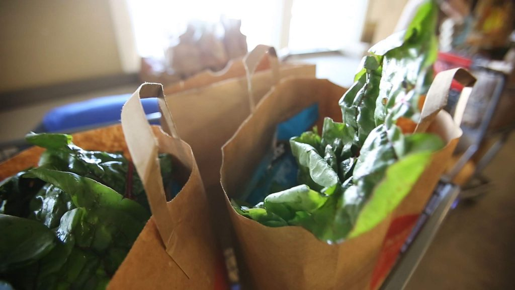 Bags of groceries containing fruits, vegetables, meat, eggs, milk, juice, and other food items are packed for those waiting to pick them up in the parking lot.