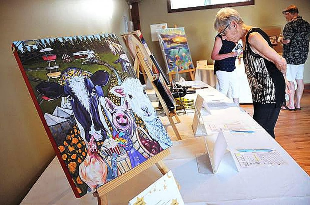 Attendees at a previous Furry, Furry Night peruse a collection of silent auction items, including a reproduction of Kathryn Wronski's 2018 Fair Poster. The donated silent auction items help raise money for AnimalSave during their largest fundraiser of the year. This year's fundraiser will happen virtually, Saturday evening, Oct. 24.
