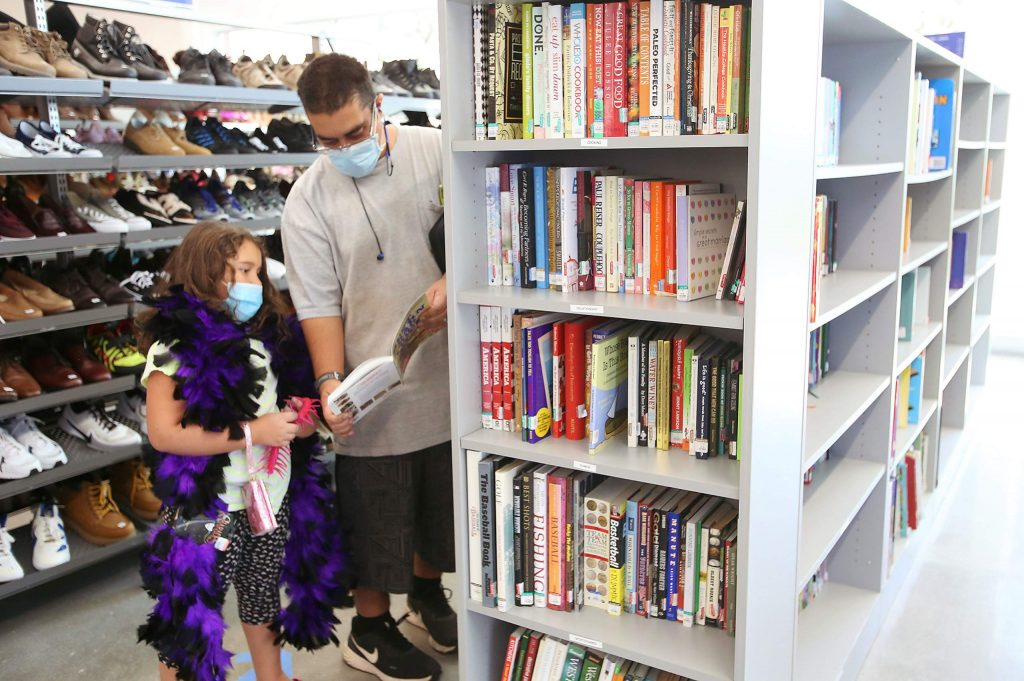 Josh Vega and daughter Emilyah Vega peruse items for sale at the new Goodwill store on Sutton Way in Grass Valley.