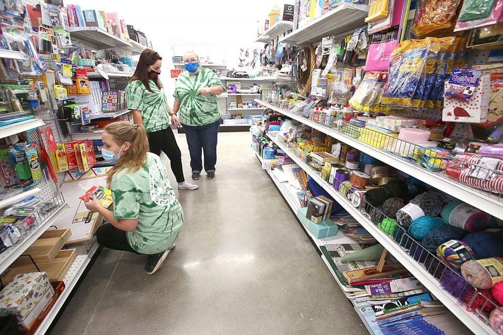 Goodwill employees help stock the shelves Tuesday during the first day of business at the new Grass Valley store on Sutton Way.