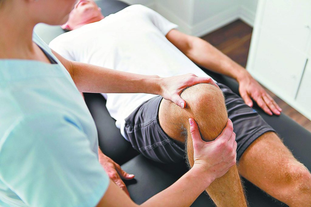 A Patient at the physiotherapy doing physical exercises with his therapist