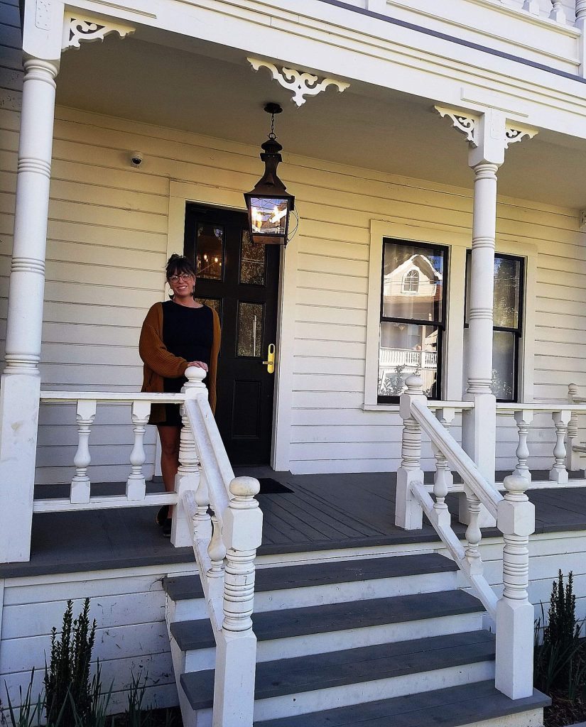 Holbrooke Hotel Sales and Events Manager Erin Lewis standing on the porch of the Purcell House.