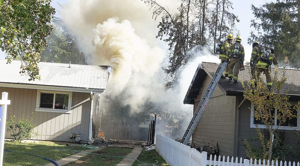 Firefighters cool the side of the empty home while others work on the burned fence beween the two structures.