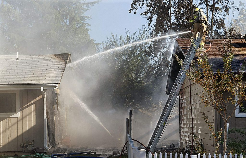 Firefighters spraying water on the second empty structure that caught on fire Sunday afternoon.
