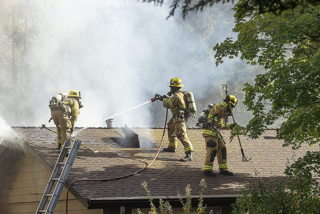 Firefighters on the roof spraying water on the fire and a hole in the roof to vent the fire in the attic.