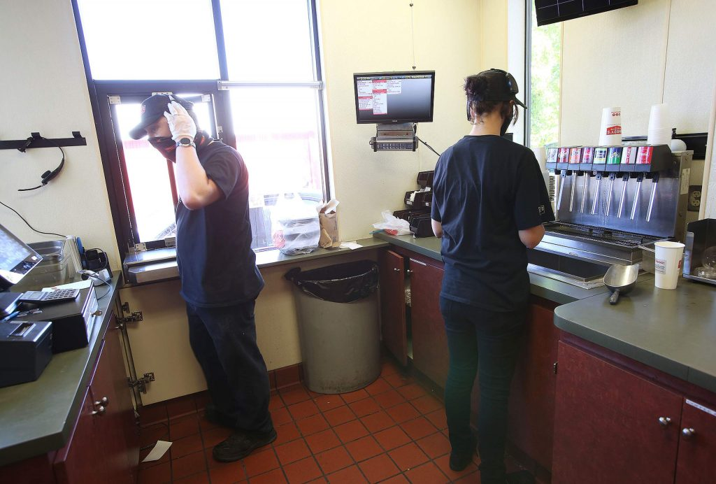 Drive-thru staff at Jimboy's take orders and hand food off through the drive-thru window Thursday in Grass Valley.
