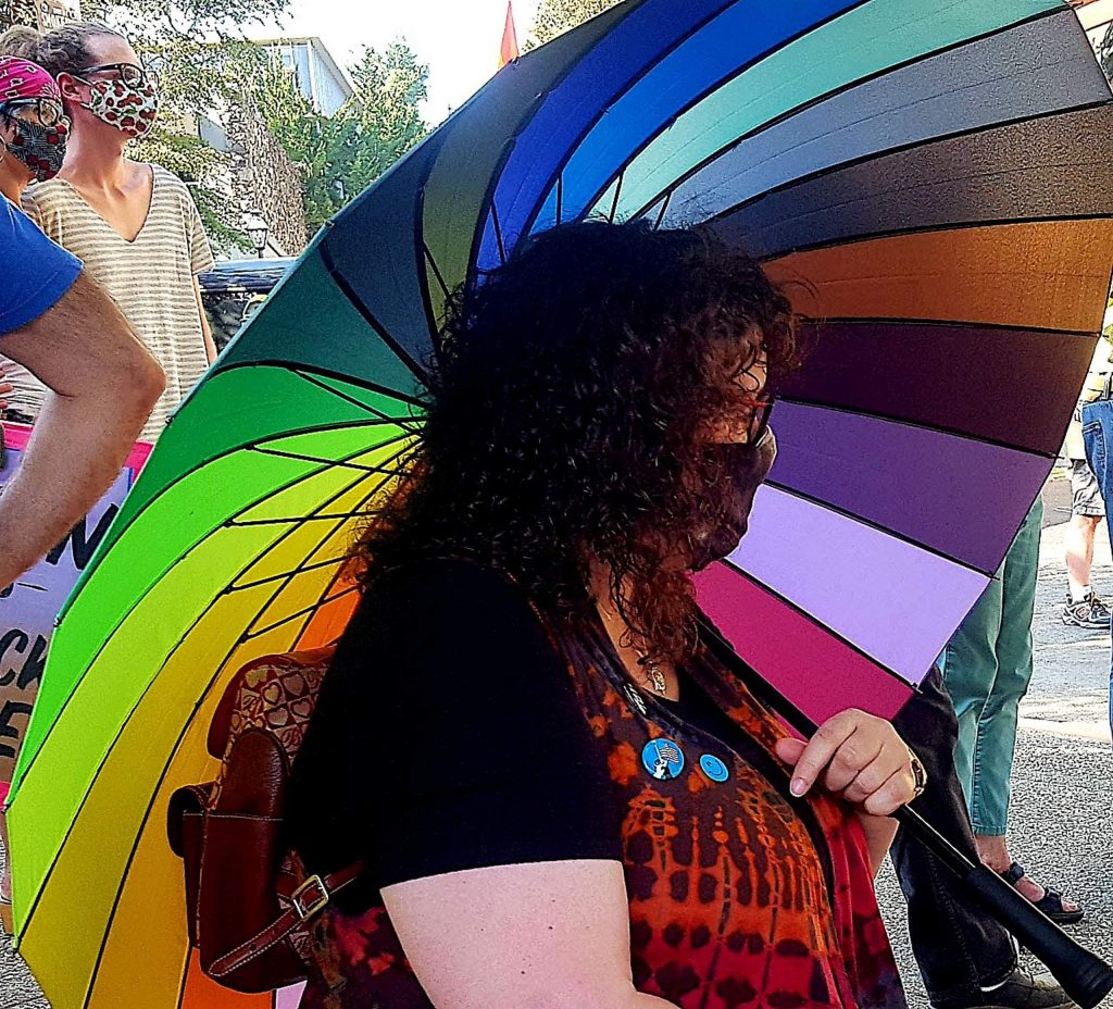A woman listens as speakers address the crowd after Sunday's March for Racial Equity, Inclusion, and Peace down Broad Street in Nevada City.