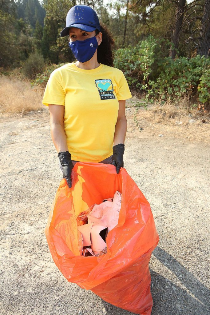 A Coldwell Banker Grass Roots Realty volunteer shows off her finds of trash picked up along the side of Sutton Way near Idaho Maryland Road Saturday.