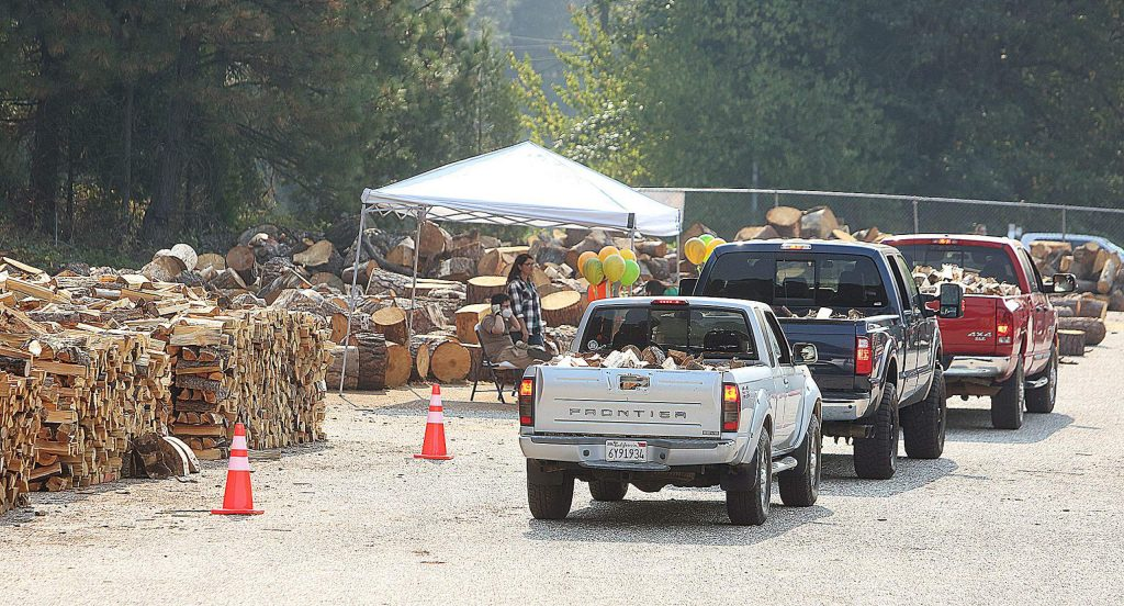 Vehicles loaded with wood and bound for the homes of local seniors leave the Rise Gold site, where the Gold Country Senior Services firewood giveaway takes place.