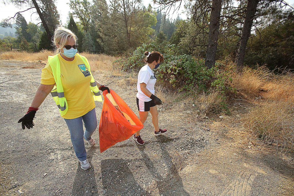 Coldwell Banker Grass Roots Realty volunteers Terri Ruggiero, left, and Diann Patton walk along Sutton Way near Idaho Maryland Road during Saturday's RAKE event.
