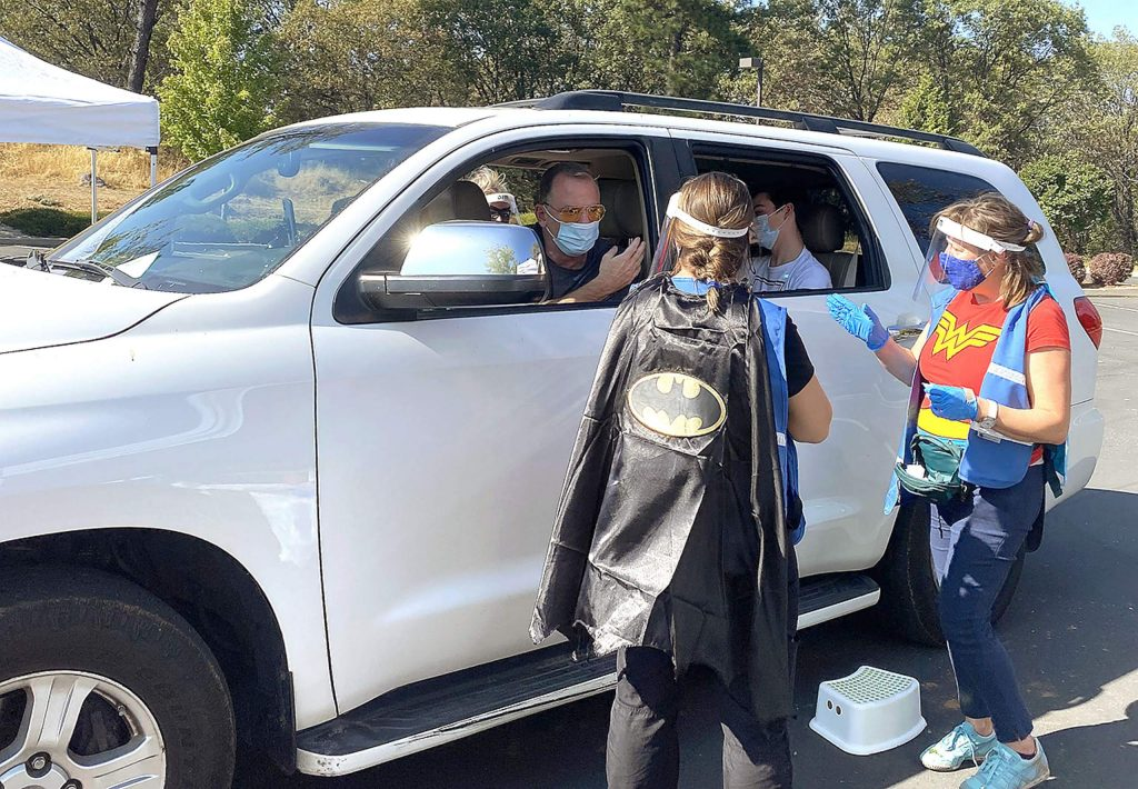 A family receives their flu shots while seated in their vehicles during Tuesday's Nevada County Public Health's free drive-thru flu shot clinic. The event helped Public Health staff practice for distributing an emergency vaccination.