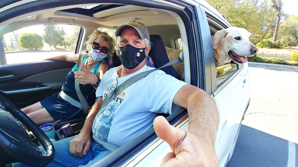The Pellizzer family, along with dog Parker, gives a thumbs up from their vehicle after getting flu shots Tuesday during Nevada County's free drive-thru flu shot clinic.