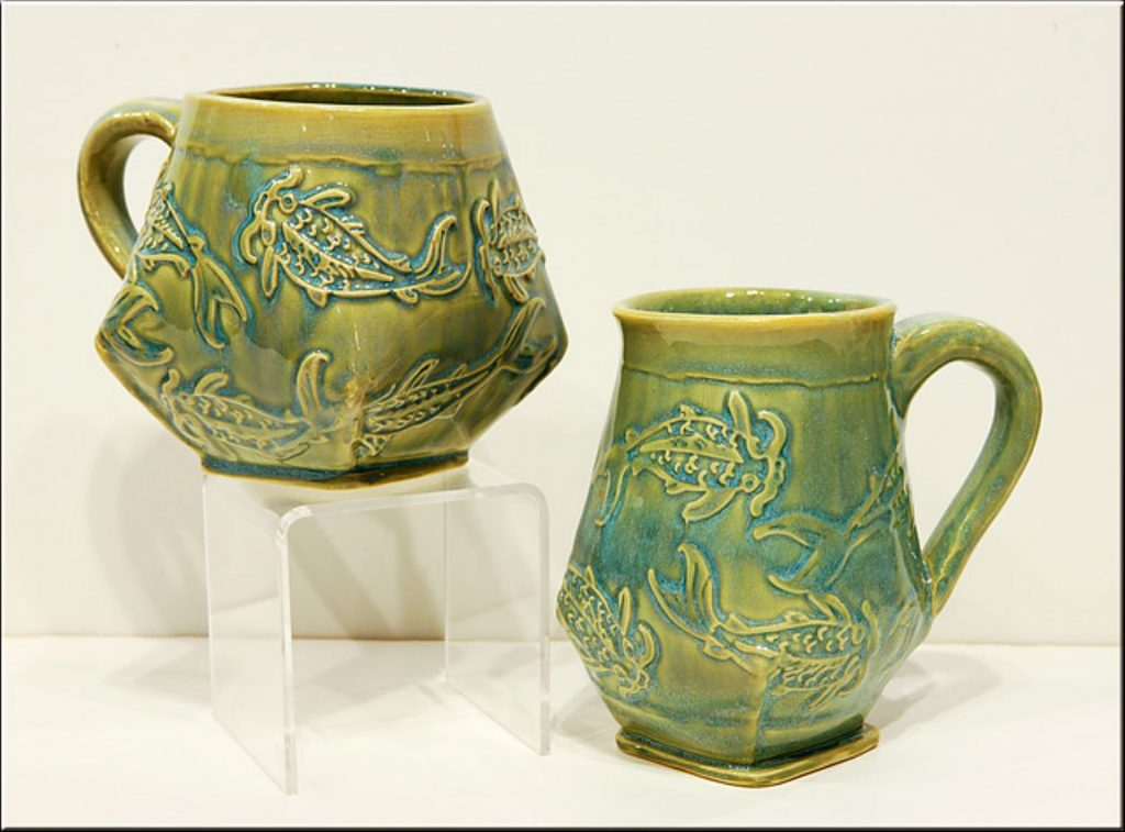 A cup and mug decorated by koi, by local artists Mindy Oberne.