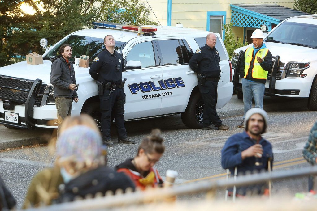 Nevada City police, PG&E employees and members of the community gathered along Broad Street at Spring Street Friday morning to watch the standoff with tree protesters unfold.