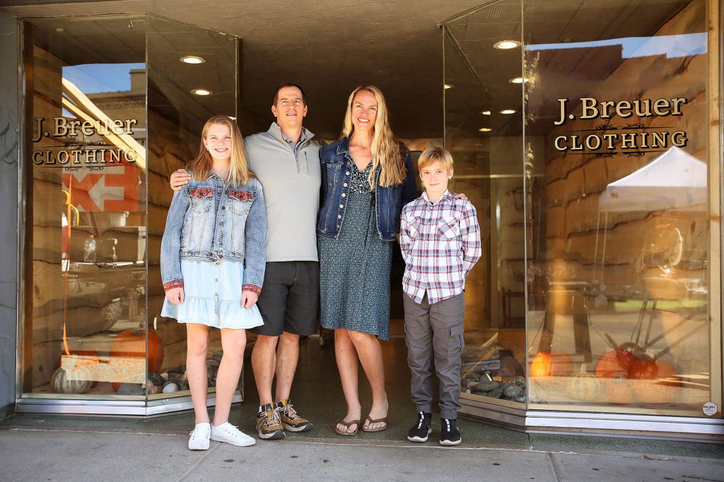 Brandon Miller and Julie Breuer, with their children Gracie and Tanner, stand in front of 141 Mill St. in downtown Grass Valley, where their clothing and apparel shop is ready to open for business.