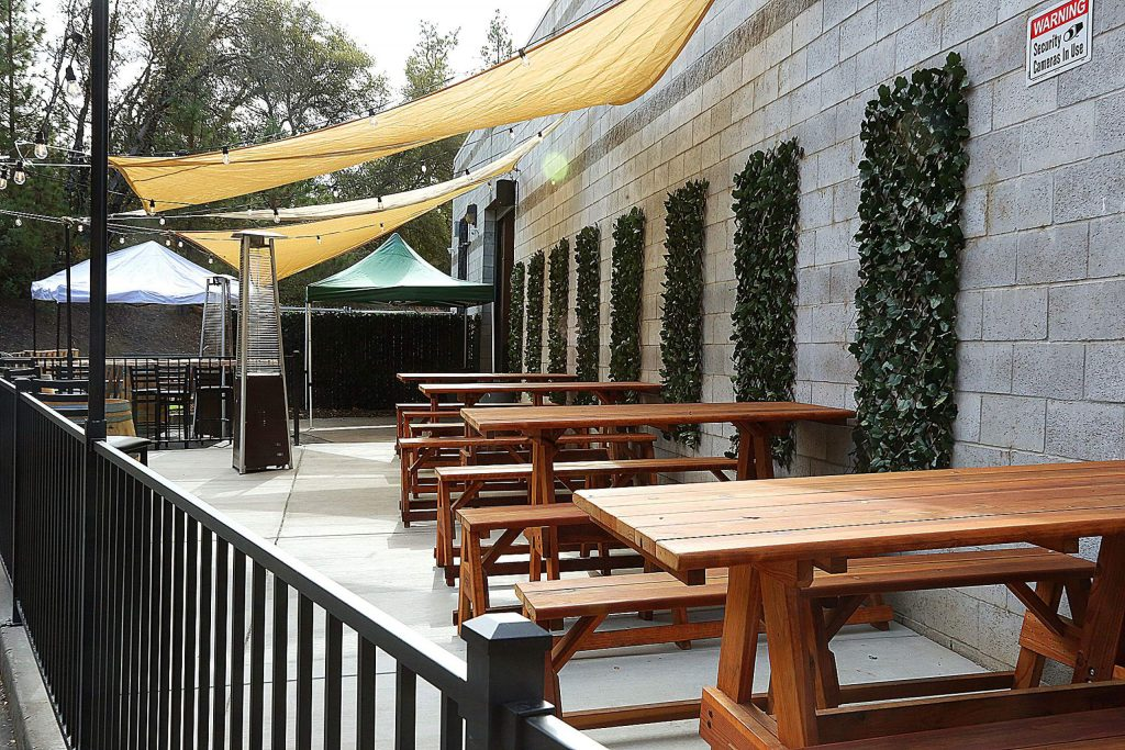 An outdoor seating area contains benches, lights, and outdoor heaters.