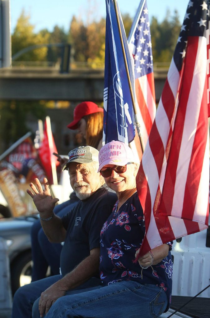 About a dozen Trump supporters wave to people along the corner of Neal and South Auburn streets Wednesday afternoon during a Trump 2020 post-election rally for America.