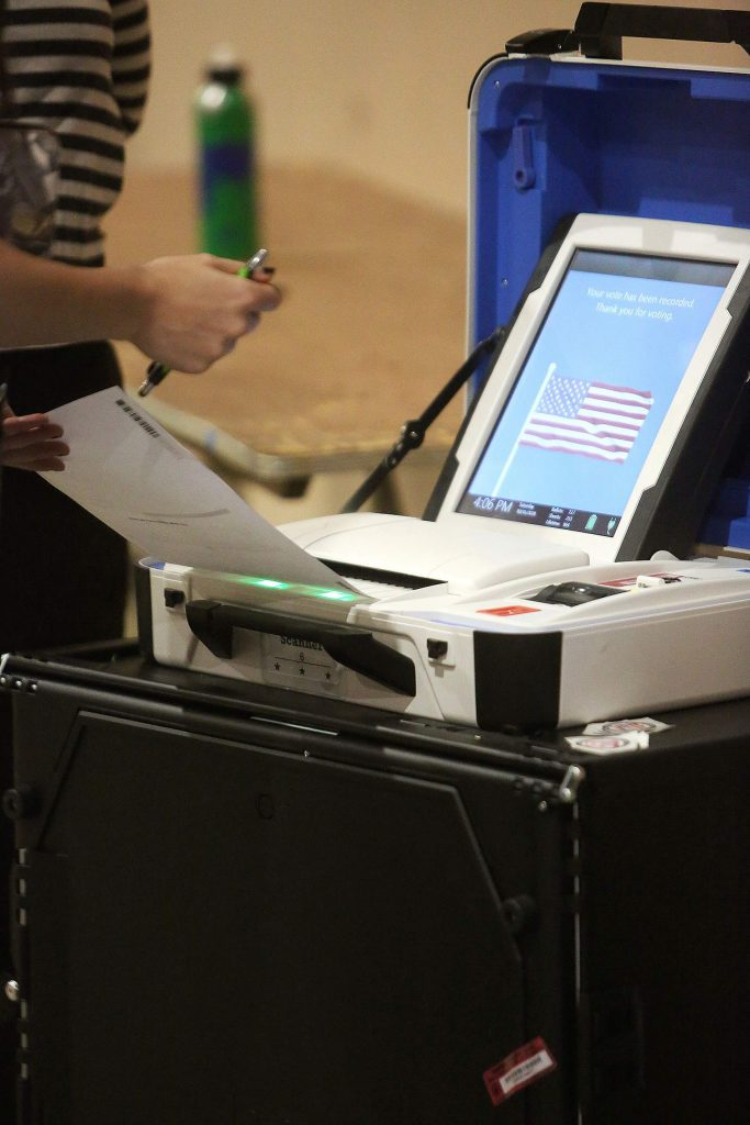 A ballot is placed into an electronic machine, which immediately tabulates votes Saturday at the Nevada County Fairgrounds vote center.