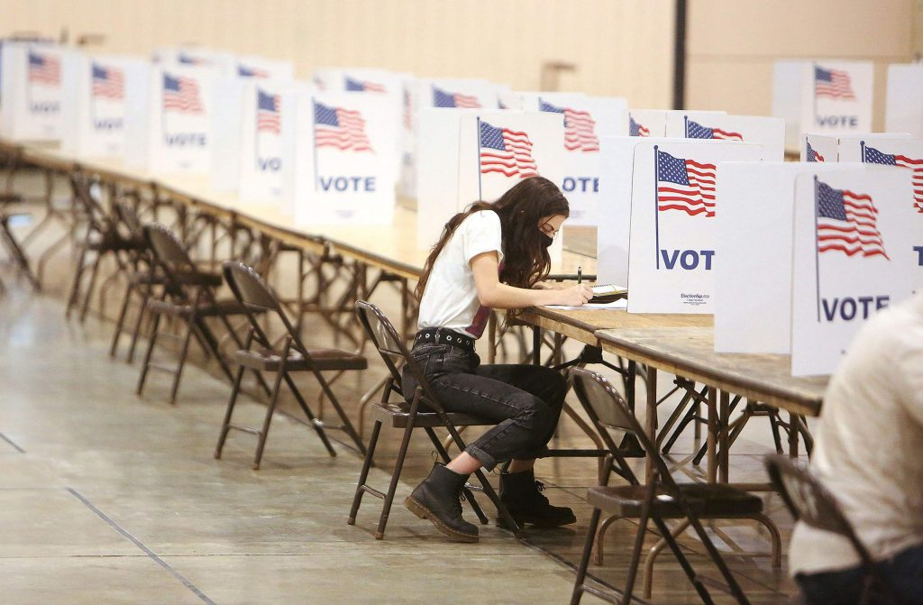 First time voter, Grass Valley's Kiave Codianne, works on filling out her ballot Saturday at the vote center inside the Main Event Hall at the Nevada County Fairgrounds.