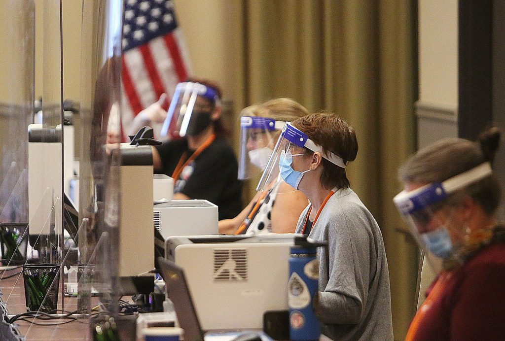 Nevada County elections workers wear face shields and work behind sheets of plexiglass while helping people get their ballots to vote Saturday at the Gold Miners Inn vote center.