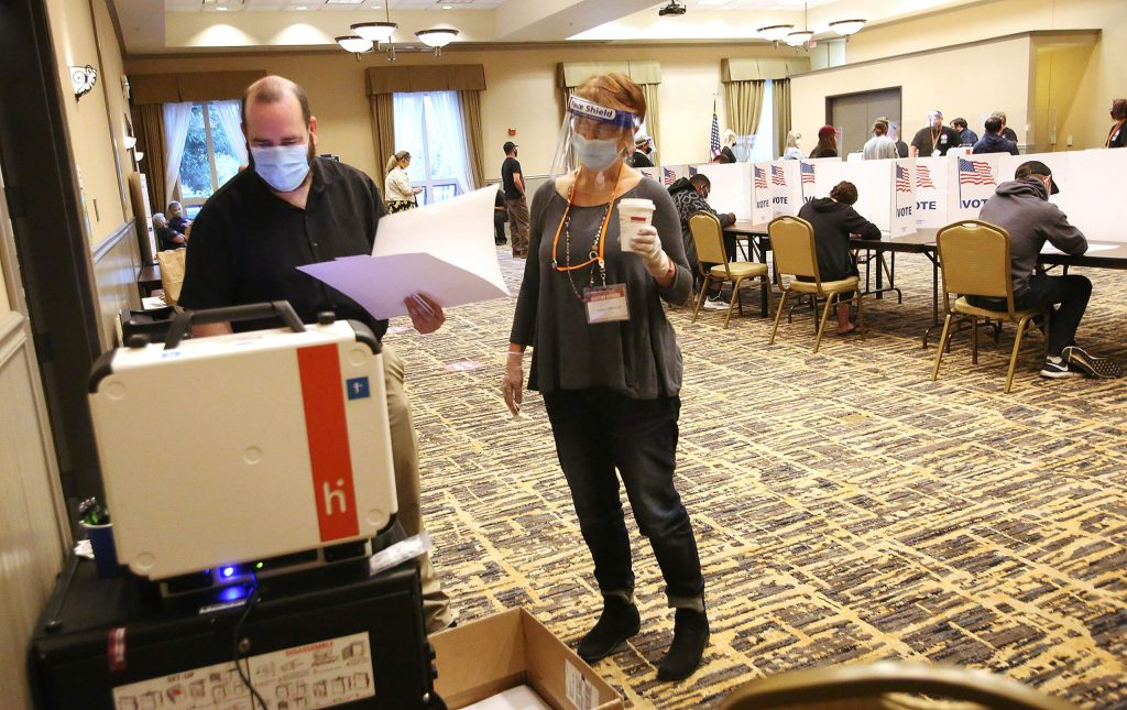 Grass Valley's Scott Naylor feeds his ballot into the machine with the help of poll worker Diane Fornasier Tuesday evening at the Gold Miners Inn vote center in Grass Valley.