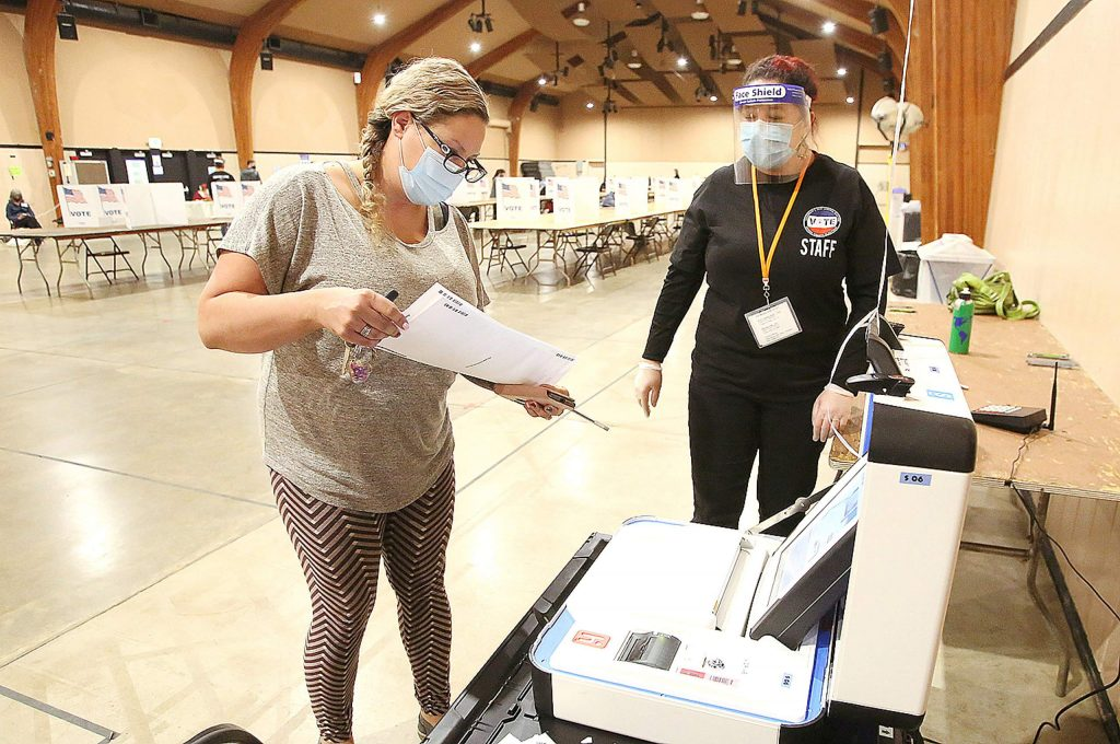 Hope Corstorphine readies to feed her ballot into the machine with the help of Nevada County poll worker Kindra Hillman Tuesday evening at the fairgrounds' vote center.