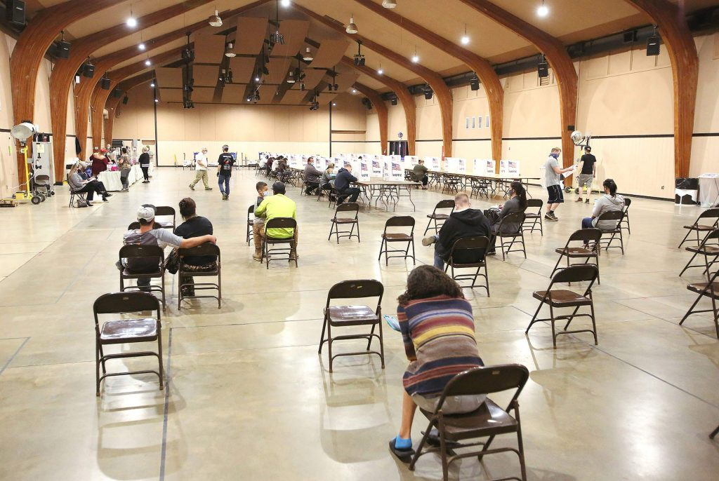Voters sit in socially distant chairs before being called up to receive their ballots and vote Tuesday at the Nevada County Fairgrounds' vote center in Grass Valley.