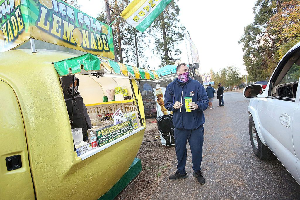 The Lemonade stand's Kyle Quint helps serve a cherry lemonade to a drive-thru customer Friday afternoon at the Nevada County Fairgrounds during Butler Amusement's Fair Food Festival going through the weekend.