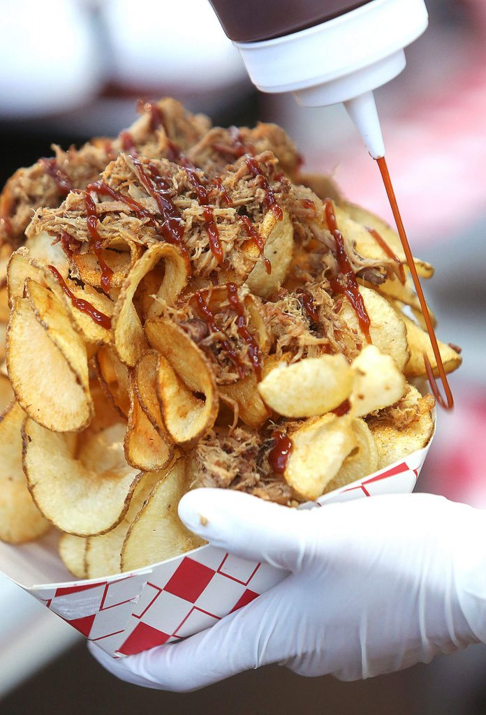 Ribbon fries loaded with barbecue pulled pork is prepared from Boguey's Chicken and Waffle's stand during the Nevada County Fairgrounds' Fair Food Festival Friday. The drive-thru food fest lasts through Sunday and is accessible through Gate No. 1 of the fairgrounds.