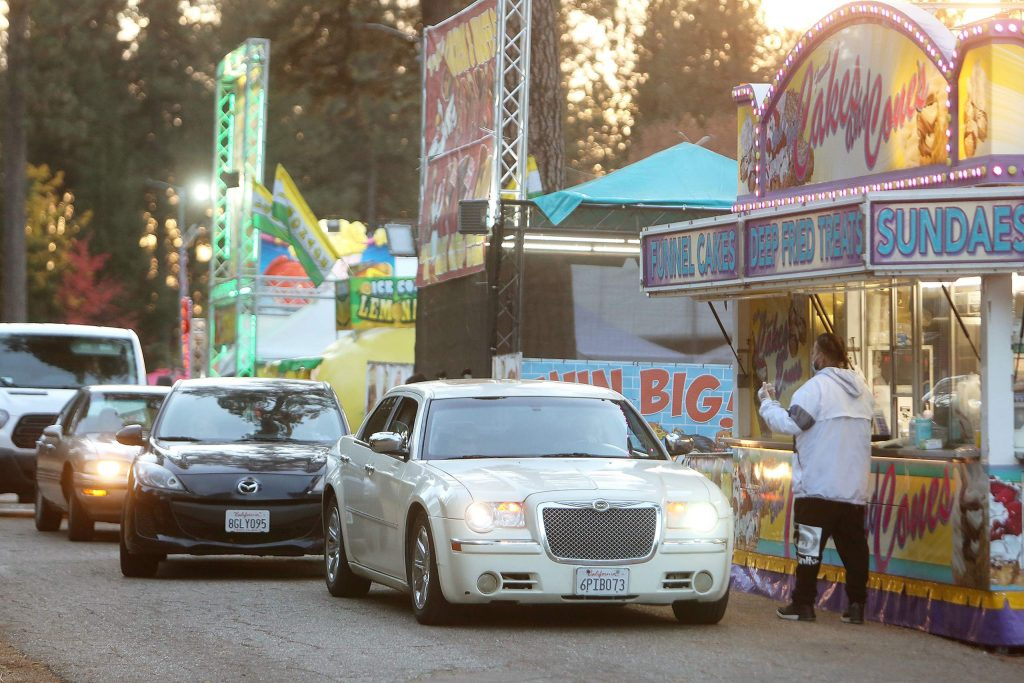 Vehicles park in front of their desired fair food stand Friday at the fairgrounds' Fair Food Festival hosted by Butler Amusements.