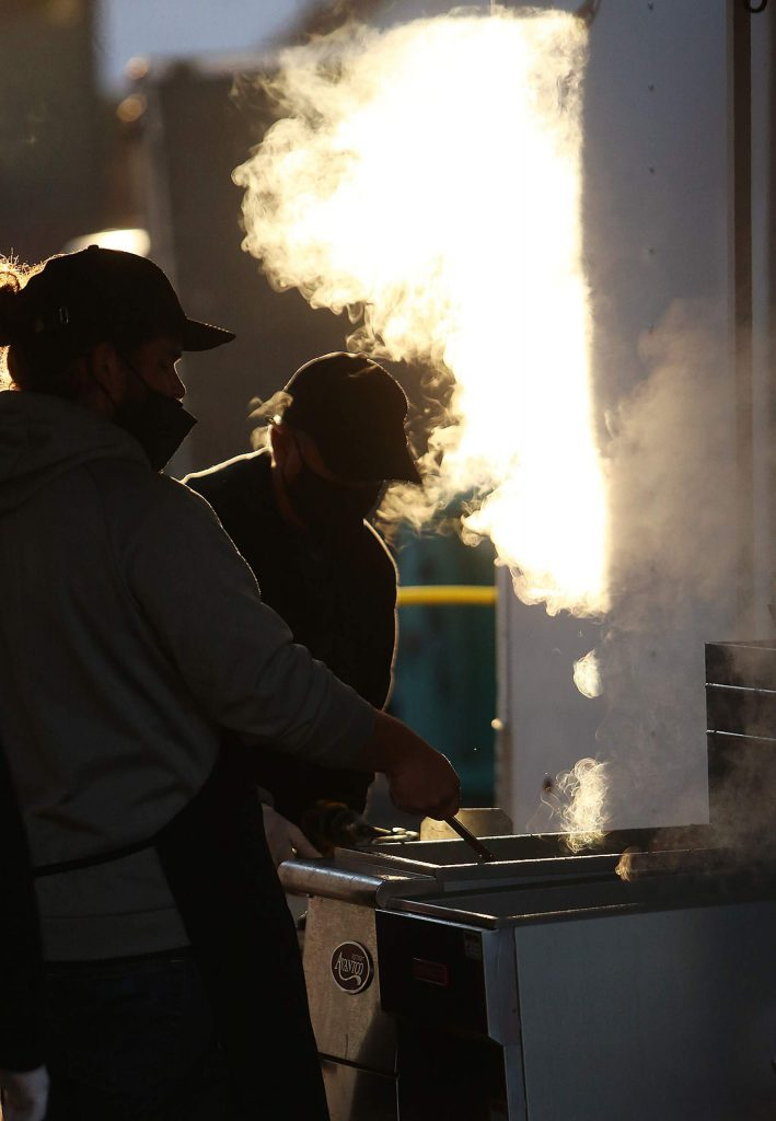 Fair food booth workers fry up a dish for Boguey's Chicken and Waffle stand.
