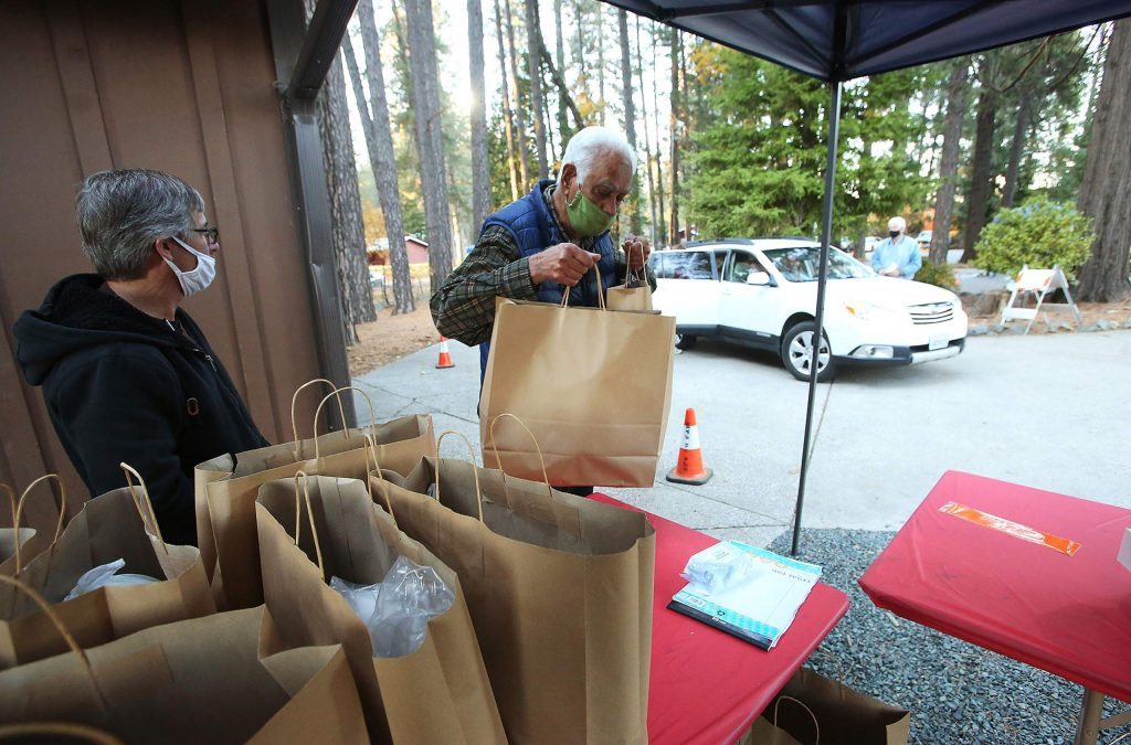 Volunteer Jivat Muki readies to load a pulled pork barbecue meal into a vehicle during Tuesday's drive-thru fundraiser for the Nevada County Fairgrounds. Tickets for the fundraiser were sold out in advance, though organizers plan to hold future meal fundraisers.
