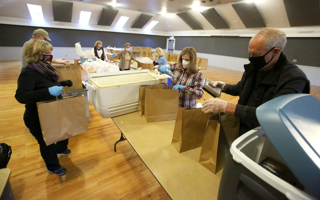 Former Nevada County Sheriff Keith Royal, right, and other volunteers help package meals inside of the Ponderosa Hall at the Nevada County Fairgrounds for Tuesday's fundraiser.