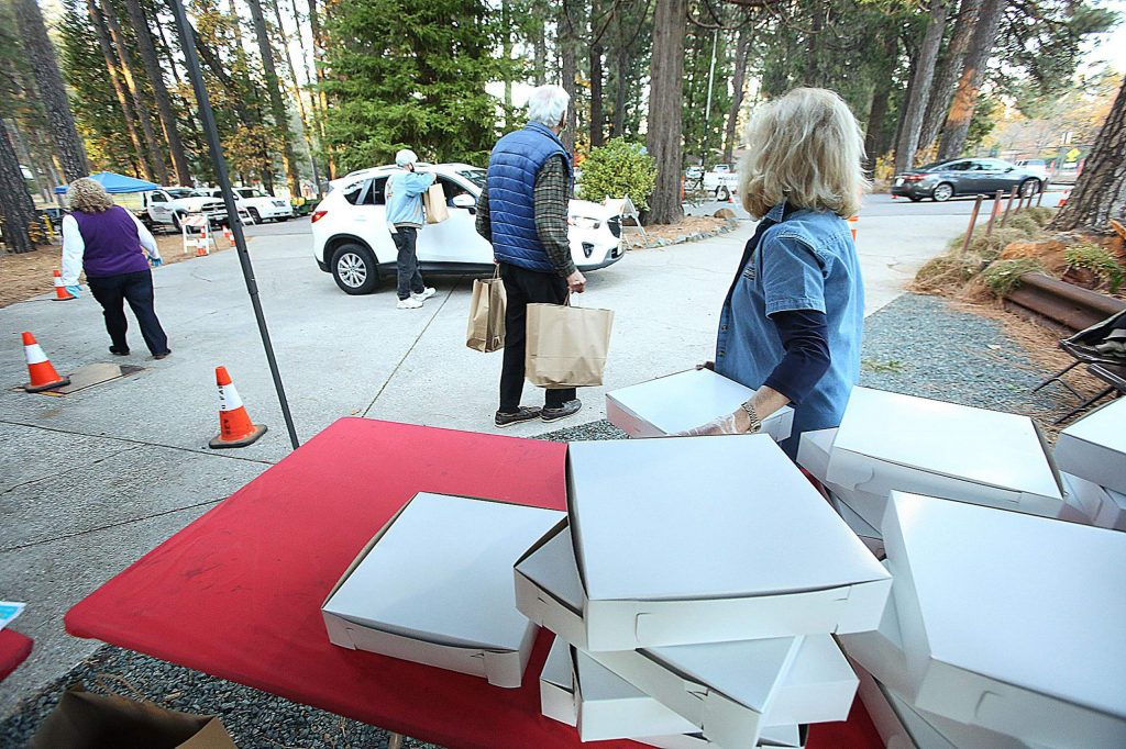 Volunteers from the Nevada County Fairgrounds Foundation, the fairgrounds Board of Directors, and the Foothill Lions Club help pass out pies and barbecue dinners during Tuesday's fundraiser to help support the fairgrounds.
