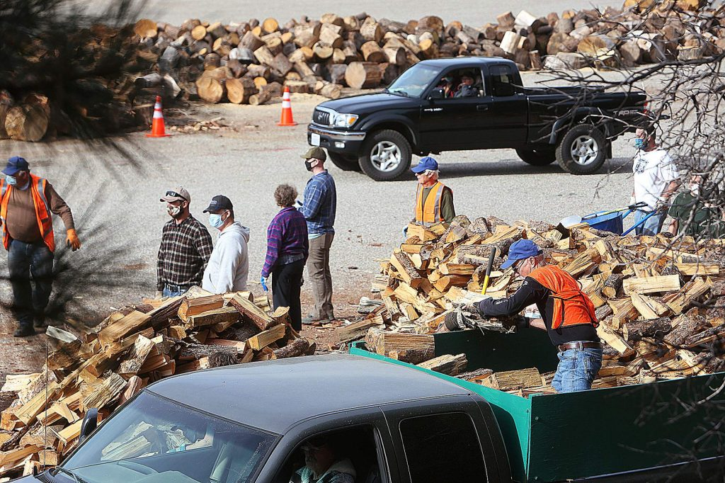 Volunteers work to help load firewood into trucks for delivery to the homes of area seniors in need of firewood for the winter. The Saturday effort was part of the Gold Country Senior Services senior firewood program.