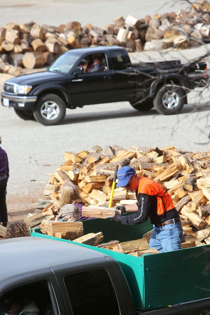 Volunteers help load hundreds of cut cords of wood into the backs of pickup trucks, onto trailers, and to the homes of Nevada County's seniors as part of the Gold Country Senior Services senior firewood program.