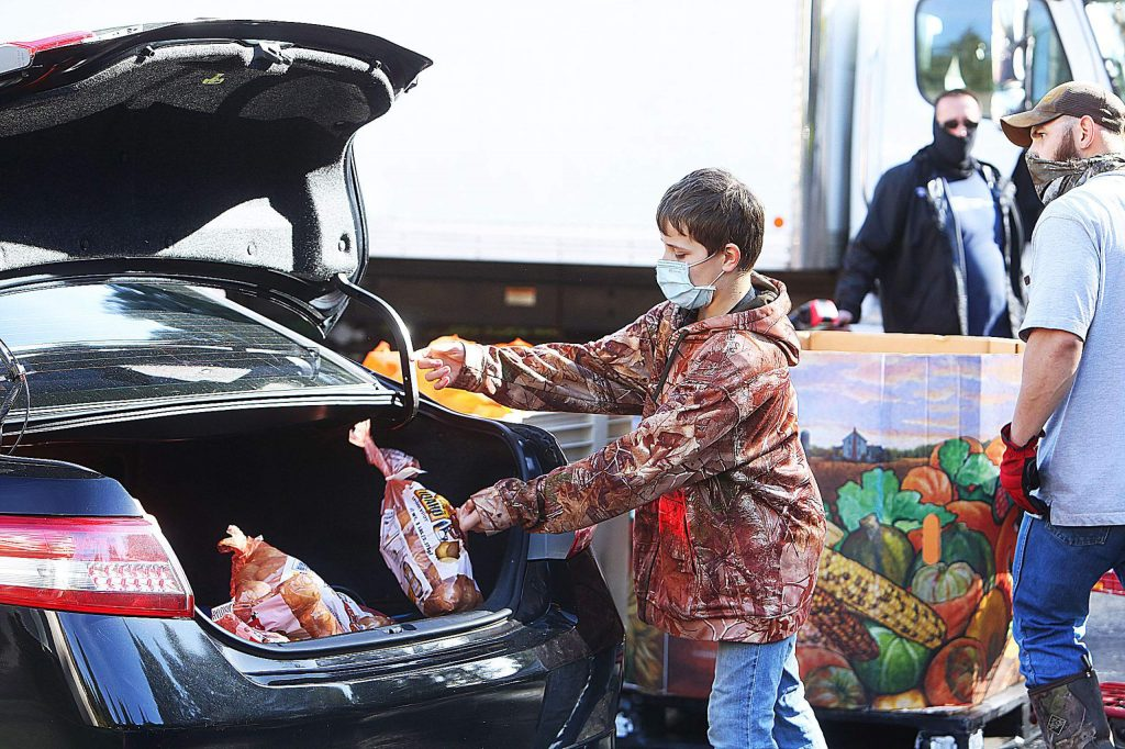 Thirteen-year-old Jeremiah Thompson helps load a trunk with potatoes during Thursday's Food Bank of Nevada County holiday food distribution.