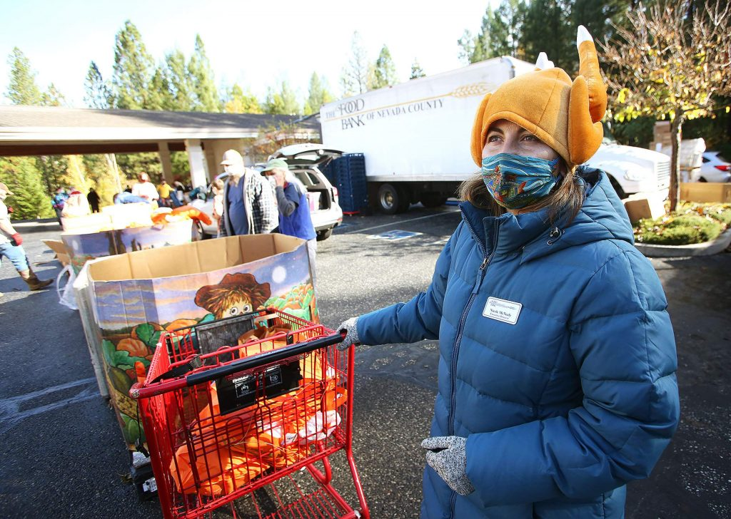 Food Bank of Nevada County Executive Director Nicole McNeely dons a festive hat while helping to fill vehicles with food for the Thanksgiving holiday during Thursday's weekly drive-thru distribution at Grass Valley Seventh-day Adventist Church off Osborne Hill Road. About 1,200 families were served Thursday, according to McNeely.
