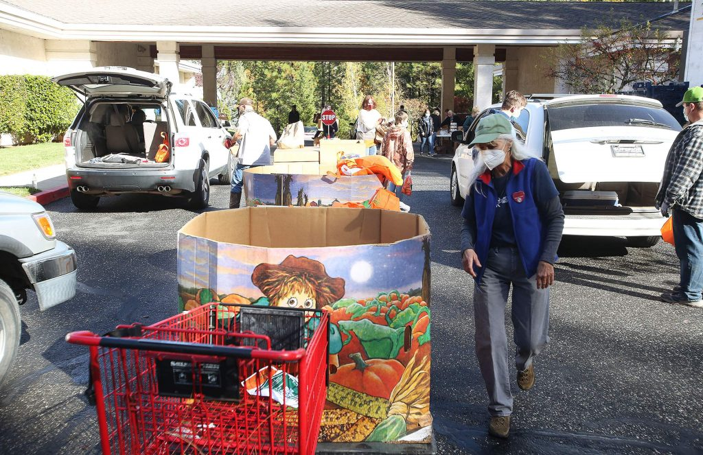 Volunteers help load food into the trunks of vehicles during Thursday's Food Bank of Nevada County holiday food distribution.