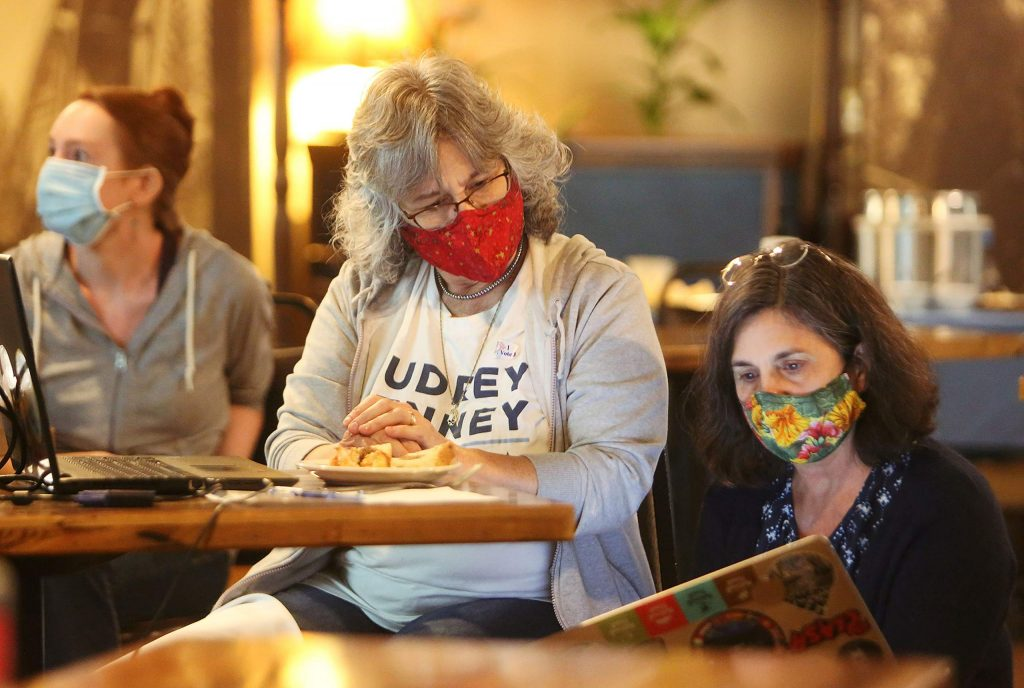 Attendees of a private election watch party held at Wild Eye Pub in Grass Valley check their laptops for election results Tuesday evening.