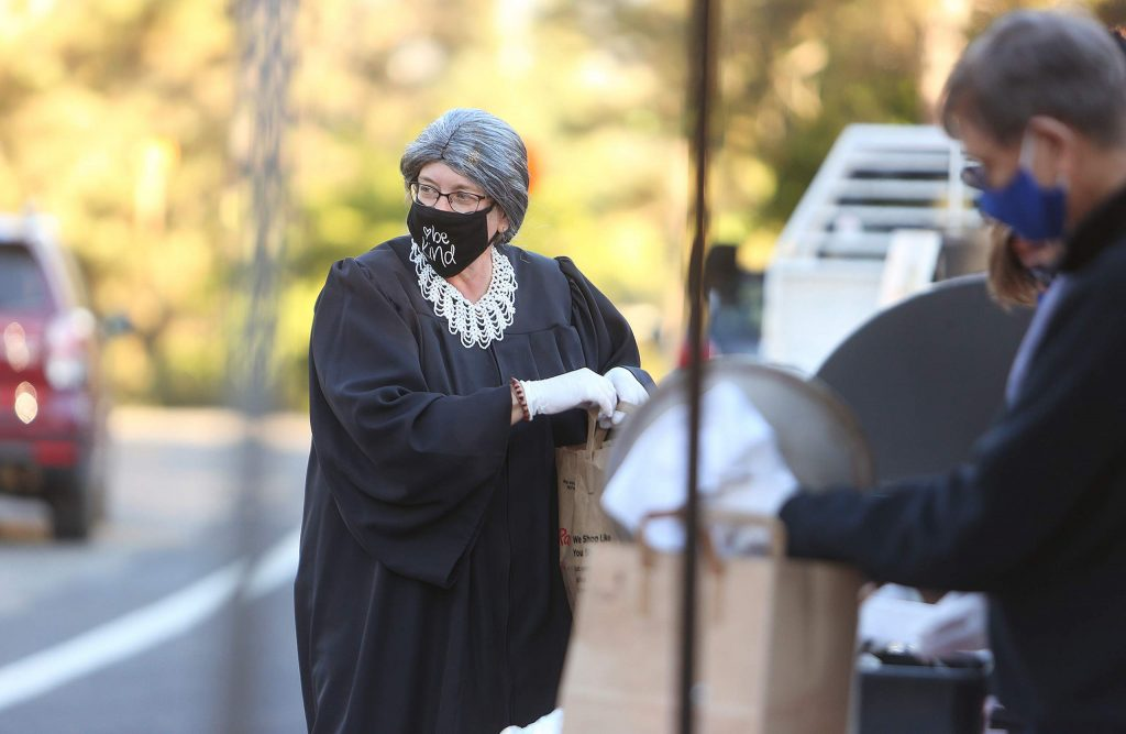 Rotary Club of Grass Valley member Viv Tipton, dressed as Ruth Bader Ginsburg, helps serve more than 200 trip-tip dinner meals at Lyman Gilmore school during a drive-thru Halloween meal fundraiser.
