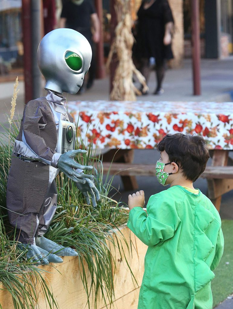 A young terrestrial is a little skeptical to meet an extra terrestrial Saturday evening along Mill Street in downtown Grass Valley.