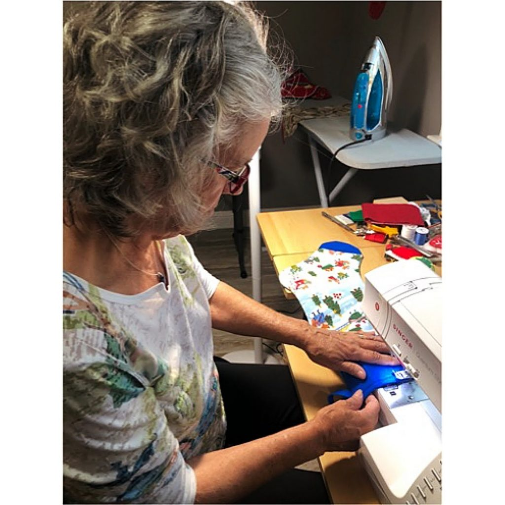 """Marty DeKay-Bemis is one of a dozen """"elves"""" who sewed holiday stockings to be filled with age-appropriate gifts for low-income children in our community through the Bright Futures for Youth """"Rocking Stockings"""" program."""