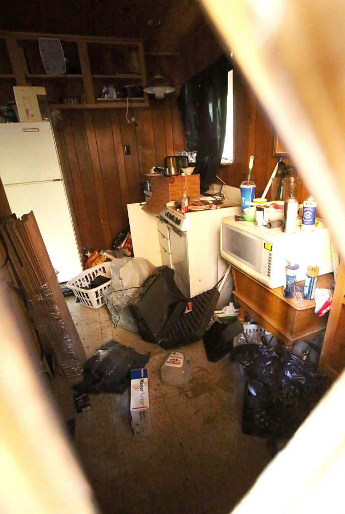 A broken window reveals a ransacked and trashed interior.