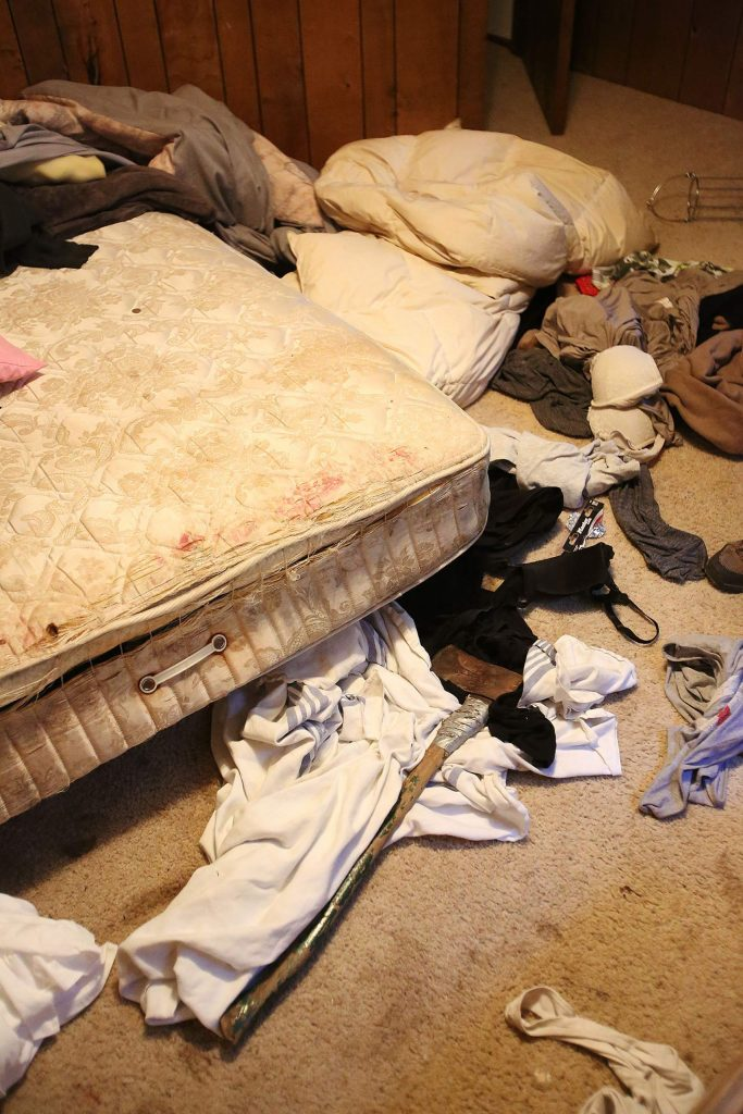 An ax sits next to a mattress in a bedroom of Marlowe's home where squatters took up residence in rural Nevada City.