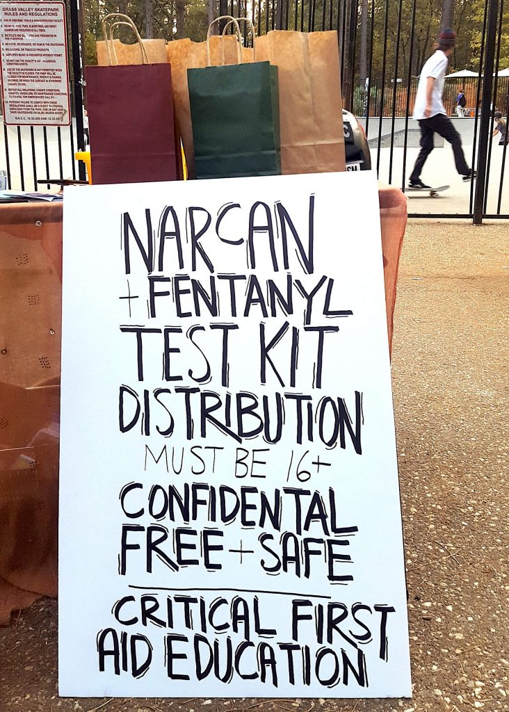 A sign advertises free Narcan and fentanyl testing kits at the skate park in Condon Park.